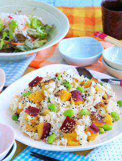 テーブルの上の皿の上に食べ物のボウルの写真・画像素材[893794]