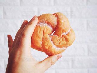 半分を握っている手は、ドーナツを食べてください。の写真・画像素材[1022299]