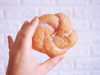 半分を握っている手は、ドーナツを食べてください。の写真・画像素材[1022465]