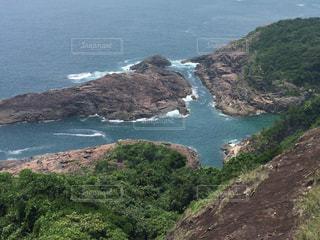 近くに水の体の横にある丘の中腹のアップの写真・画像素材[1526841]