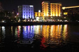 水の体の前に夜の街の景色の写真・画像素材[712814]
