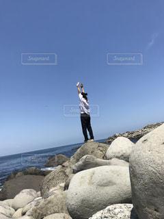 岩が多い丘の上のトリックを行う人の写真・画像素材[1185819]