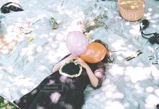木漏れ日でピクニックする女の子の写真・画像素材[1061045]