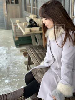 雪の中でベンチに座る女性の写真・画像素材[1670862]