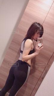 鏡の前に立っている女性がカメラのポーズをとっているの写真・画像素材[2106720]