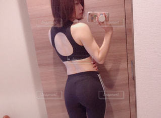 鏡の前に立っている女性がカメラのポーズをとっているの写真・画像素材[2106722]
