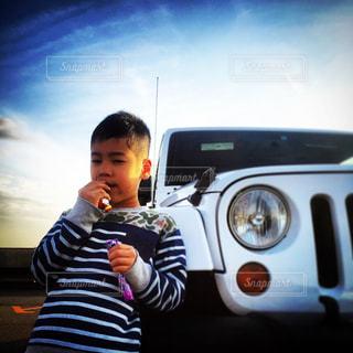 車の前にカメラを保持している男の写真・画像素材[1617256]