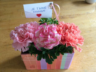 テーブルの上のピンクの花で一杯の花瓶の写真・画像素材[746388]