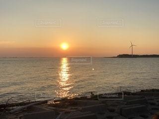 海の横にあるビーチに沈む夕日の写真・画像素材[1764646]