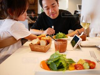 食事中にiPhoneに夢中になる子供 それを見守る親の写真・画像素材[1832831]