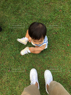 芝生に座っている女の子とママの足の写真・画像素材[1848411]