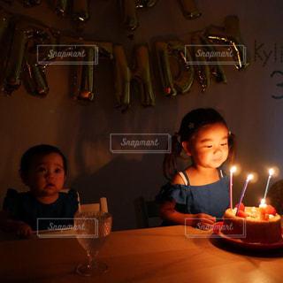 キャンドルに火がついたバースデーケーキを持ってテーブルに座っている人の写真・画像素材[2232688]