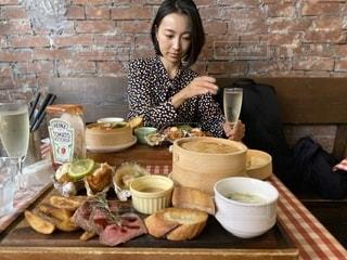食べ物を食べているテーブルに座っている女性の写真・画像素材[2708221]