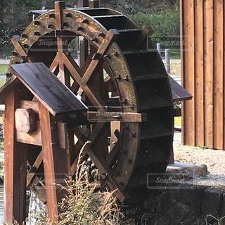 近くに古い水車のアップの写真・画像素材[1088154]