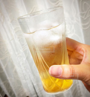 梅酒のグラスを持っている手の写真・画像素材[822276]