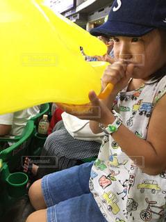 風船を膨らます少女の写真・画像素材[720444]
