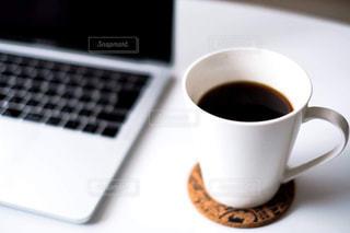一杯のコーヒーとテーブルの上に座っているラップトップ コンピューターの写真・画像素材[1792531]