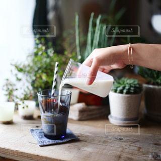 一杯のコーヒーをテーブルに座っている女性の写真・画像素材[1148740]