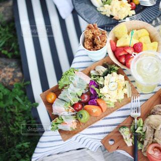 食品のプレートをテーブルに座っている人々 のグループの写真・画像素材[1186702]