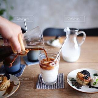 テーブルに食べ物のプレートを持っている人の写真・画像素材[1211341]