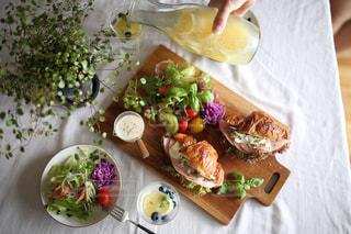 食品のプレートをテーブルに着席した人の写真・画像素材[1300435]