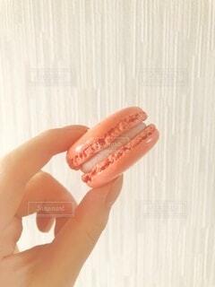 ピンクのマカロンを持つ手の写真・画像素材[4918721]