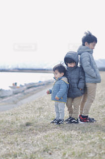 草の中に立っている小さな男の子の写真・画像素材[3061206]