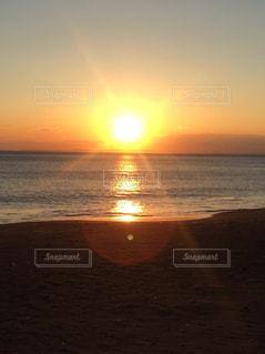 海の横にあるビーチに沈む夕日 - No.917060