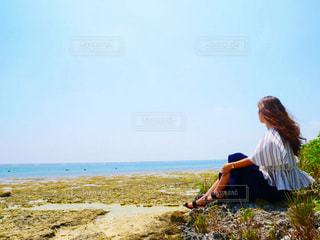 ビーチに座っている女の写真・画像素材[1111952]