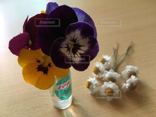 テーブルの上に紫色の花を詰めた花瓶の写真・画像素材[2139341]