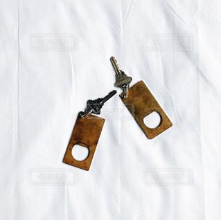 ベッドの上に置かれたホテルの部屋の鍵の写真・画像素材[958996]