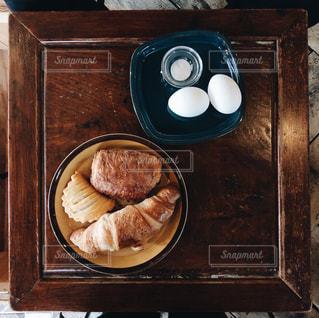 木製テーブルの上のパンとゆで卵の写真・画像素材[959612]