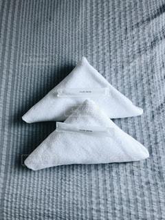 ベッドの上に置かれたバスタオルと歯ブラシの写真・画像素材[961540]