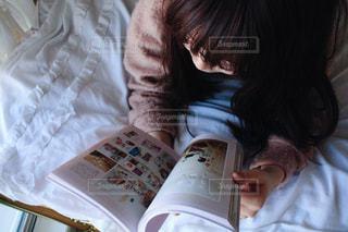 ベッドの上で本を読んでいる女性の写真・画像素材[965924]