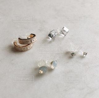 大理石風の床に置かれたピアスの写真・画像素材[978264]