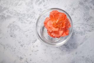 水を入れたボウルの横のオレンジ ジュースのガラスの写真・画像素材[978713]