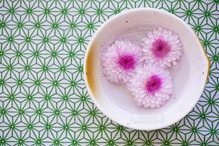 テーブルの上のピンクの花で満ちているプレートの写真・画像素材[1153642]