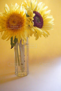 テーブルの上に花瓶に黄色い花の写真・画像素材[1316876]