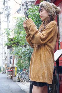 携帯電話で話している帽子をかぶっている女性の写真・画像素材[1542578]