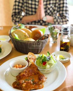 食品のプレートをテーブルに着席した人 - No.1210537