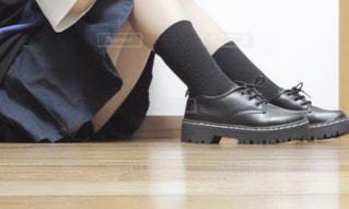 いくつかの靴で、テーブルに座っている人の写真・画像素材[1154291]