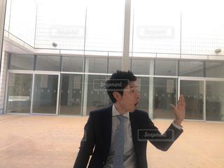 建物の前に立っているスーツの男の写真・画像素材[1016287]