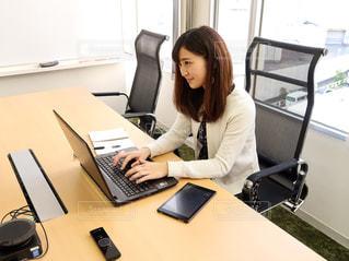 ノート パソコンを机に座って、カメラで笑顔の女性の写真・画像素材[1835578]