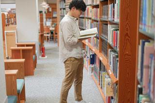 本棚の隣に立っている男の写真・画像素材[2506796]