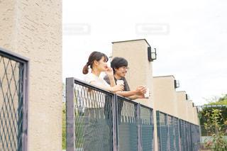 フェンスの前に立っている男女の写真・画像素材[2509359]