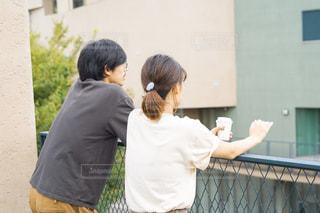 フェンスの隣に立っている男女の写真・画像素材[2509361]