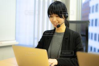 ラップトップを使ってテーブルに座っている人の写真・画像素材[2995217]