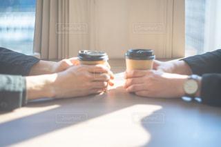 コーヒーを飲みながらテーブルに座っている人の写真・画像素材[3053421]