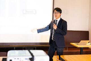 机の前に立っているスーツを着た男の写真・画像素材[4023095]