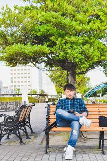 公園のベンチに座っている人の写真・画像素材[2511018]
